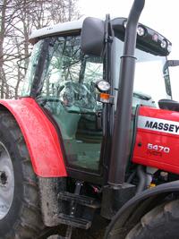 Traktorn har sidomonterat avgasrör och stora dörra. Det går bra även att använda höger dörr.